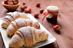 Croissant e un inceppamento di fragola sui precedenti di legno Fotografia Stock
