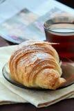 Croissant e una tazza di tè immagine stock