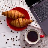 Croissant e xícara de café com o portátil na tabela de madeira imagem de stock