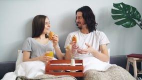 Croissant eaing dos pares alegres na cama que conversa e que ri apreciando a manhã video estoque