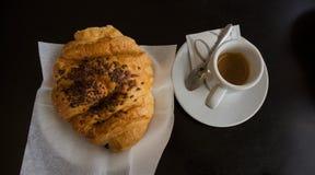 Croissant et café avec la table noire sur le fond Image stock