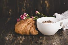 Croissant et cappuccino frais au-dessus de table en bois Photos stock