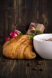 Croissant et cappuccino frais au-dessus de table en bois Photo stock