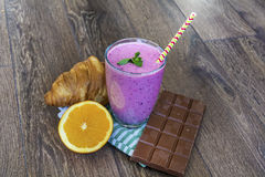 Croissant,forest fruits smoothie ,orange and chocolate stock photography