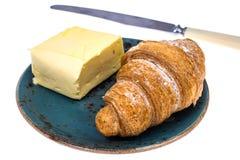 Croissant frais avec du beurre du plat bleu sur le fond blanc Photographie stock