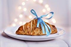 Croissant frais avec le ruban bleu sur un fond de bokeh Photos libres de droits