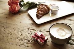 Croissant frais de boulangerie, café avec le signe de coeur, fleurs roses sur la table en bois Le petit déjeuner romantique pour  Image stock