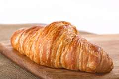 Croissant français floconneux entier sur un conseil Photo stock