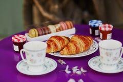 Croissant franceses, bolinhos de amêndoa e duas xícaras de café no café exterior parisiense Imagem de Stock Royalty Free