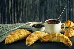 Croissant freschi con caffè ed inceppamento su un fondo di legno scuro fotografia stock libera da diritti