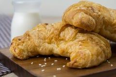 Croissant freschi con latte e sesamo bianco sul fondo del tessuto Immagini Stock
