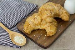Croissant freschi con latte e sesamo bianco sul fondo del tessuto Fotografia Stock