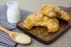 Croissant freschi con latte e sesamo bianco sul fondo del tessuto Fotografie Stock