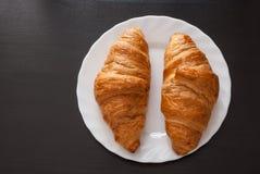 Croissant fresco e saporito sul piatto bianco sopra fondo di legno Fotografia Stock