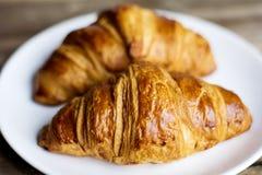 Croissant fresco su un piatto bianco Fotografie Stock