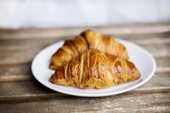 Croissant fresco in un piatto bianco Immagini Stock