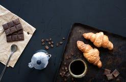 Croissant frescos com café, chocolate, fabricante de café do geyser, feijões de café no fundo escuro do vintage Pequeno almoço co fotos de stock royalty free