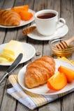 Croissant frescos com caqui e copo do chá fotografia de stock royalty free