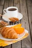 Croissant frescos com caqui e copo do chá imagens de stock royalty free