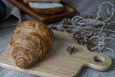 Croissant frescos em uma placa de desbastamento de madeira imagem de stock royalty free