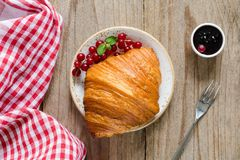 Croissant with fresh berries and jam on old wooden table. Top view, horizontal Stock Photography