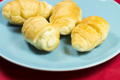Croissant. Fresh croissant on blue plate. Red background Royalty Free Stock Photo