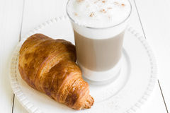 Croissant and glass of latte macchiato on white plate Stock Images