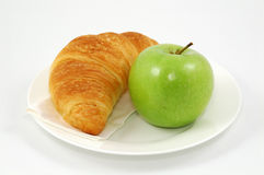 Croissant and green apple on plate Stock Photography