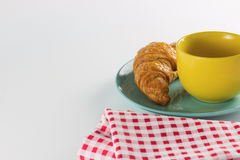 Croissant on green dish with yellow cup coffee and fabric red alternating white. Croissant on green dish with yellow cup coffee and fabric red alternating white Royalty Free Stock Images