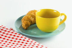 Croissant on green dish with yellow cup coffee and fabric red alternating white. Croissant on green dish with yellow cup coffee and fabric red alternating white Stock Photo