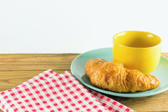 Croissant on green dish with yellow cup coffee and fabric red alternating white. Croissant on green dish with yellow cup coffee on wood, white background Stock Photo