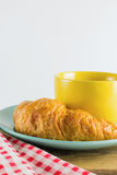 Croissant on green dish with yellow cup coffee and fabric red alternating white. Croissant on green dish with yellow cup coffee on wood, white background Royalty Free Stock Images