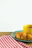 Croissant on green dish with yellow cup coffee and fabric red alternating white. Croissant on green dish with yellow cup coffee on wood, white background Royalty Free Stock Image