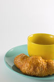 Croissant on green dish with yellow cup coffee. Croissant on green dish with yellow cup coffee on white background Stock Photos