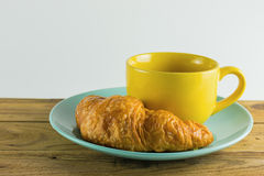 Croissant on green dish with yellow cup coffee. Croissant on green dish with yellow cup coffee on wood, white background Royalty Free Stock Photos