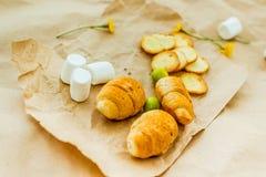 Croissant, guimauve, croûtons de pain, olives, fleurs, papier d'emballage photographie stock libre de droits