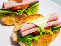 Croissant with ham cheese and lettuce. On white plate Stock Photo