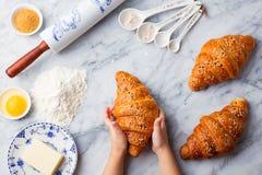Croissant, ingredienti bollenti con le mani dei bambini fotografie stock libere da diritti
