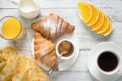 Croissant jam coffee orange jice at white wooden table. Stock Photos