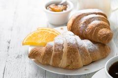 Croissant jam coffee orange jice at white wooden table. Stock Image