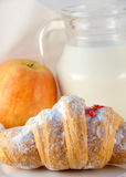 Croissant with jam and a jug of milk and an apple Royalty Free Stock Image