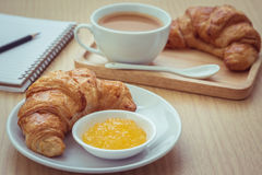 Croissant with jam on plate and coffee cup, book Royalty Free Stock Photo