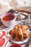 Croissant with jam and tea in the service tray close up image Royalty Free Stock Images