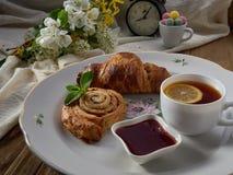 Croissant, jam, thee met citroen, op een porseleinschotel royalty-vrije stock fotografie