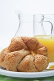 Croissant and Juice Breakfast. A continental breakfast setting.  A croissant on a white china plate with a green gingham tablecloth beneath in the foreground Stock Photography