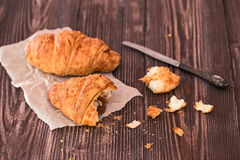 Croissant and knife for breakfast on a dark wooden table Stock Photography