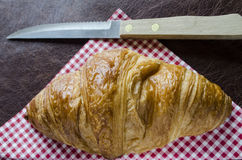 Croissant and knife on a gingham nankin Royalty Free Stock Photos