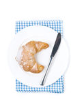 Croissant and a knife on a plate isolated Stock Photography