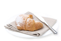 Croissant and a knife on a white plate, isolated Royalty Free Stock Images
