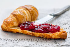 Croissant with lingonberry jam. Royalty Free Stock Image